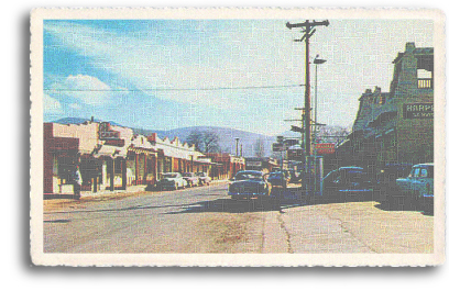A view of Kit Carson Road in downtown Taos, New Mexico (circa 1940s). Named after the famed mountain man, Kit Carson, the road is a main byway lined with galleries, shops and other businesses, leading to the location of the historic Kit Carson Home and Museum.